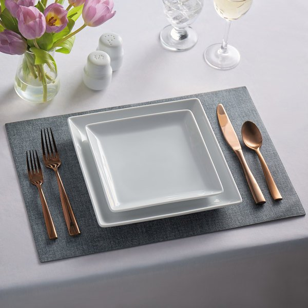 Elegant place setting features a gray woven vinyl placemat, gold silverware, and tulips