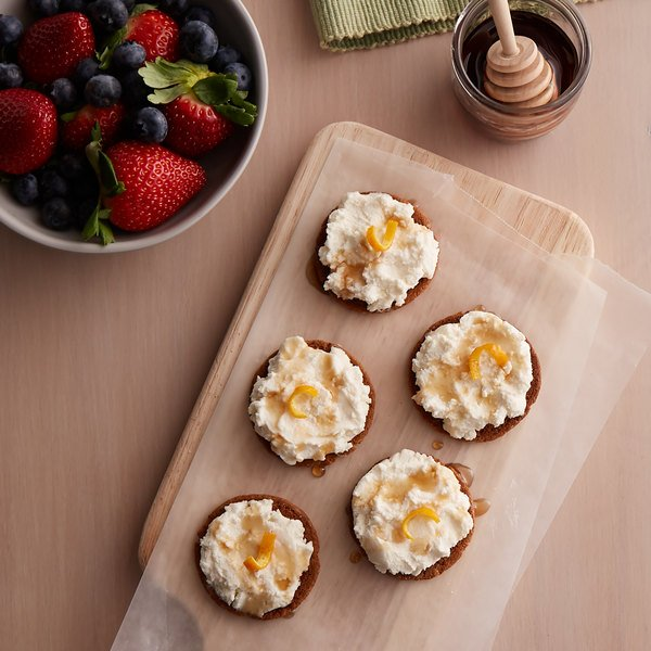 Five rounds covered with chevre and drizzled with honey on a wood serving board