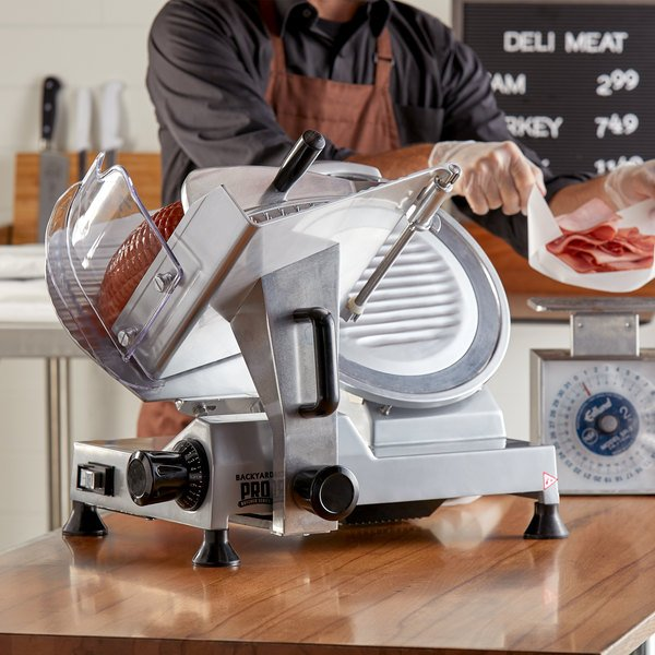 Backyard Pro entry level meat slicer on a counter with a worker slicing a ham