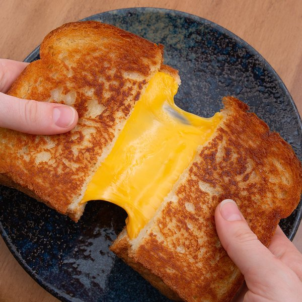 Hands splitting a toasted cheese sandwich over a plate, American cheese oozing from the center