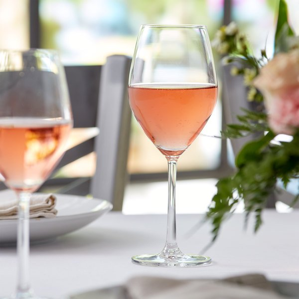 Standard red wine glass filled with rose-colored wine on an elegant table