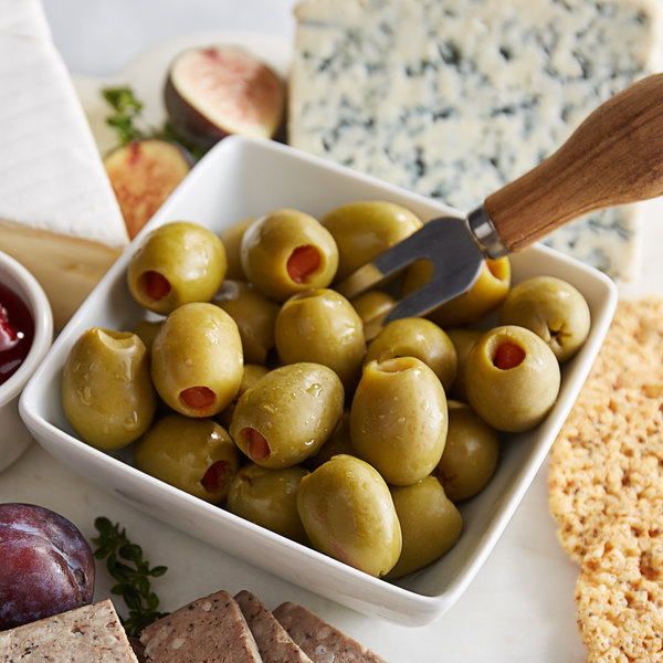 A square bowl full of pimento stuffed olives