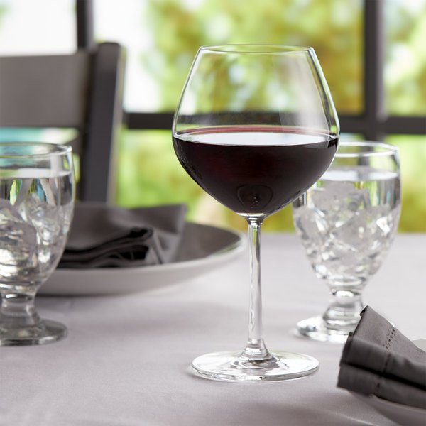 Burgundy wine glass filled with burgundy wine on an elegant table