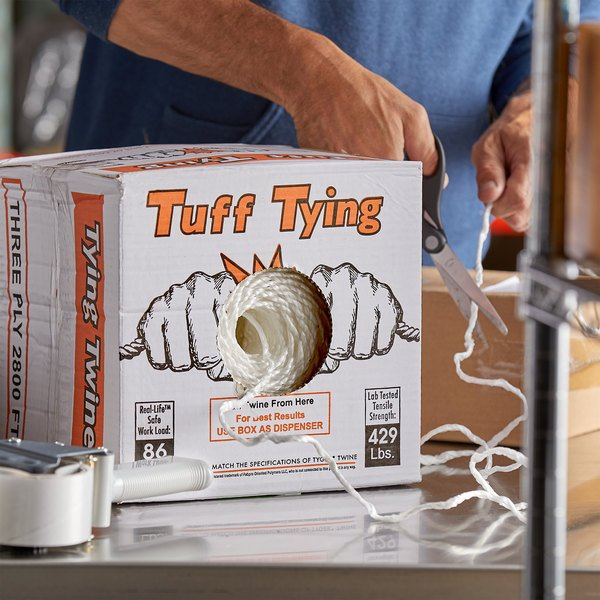 Person cutting twine with scissors from box of Tuff Tying industrial twine