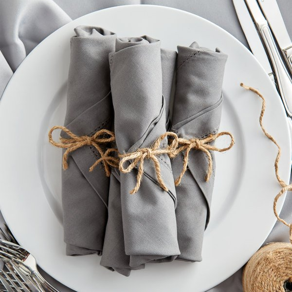 Gray napkins tied with jute twine on white plate