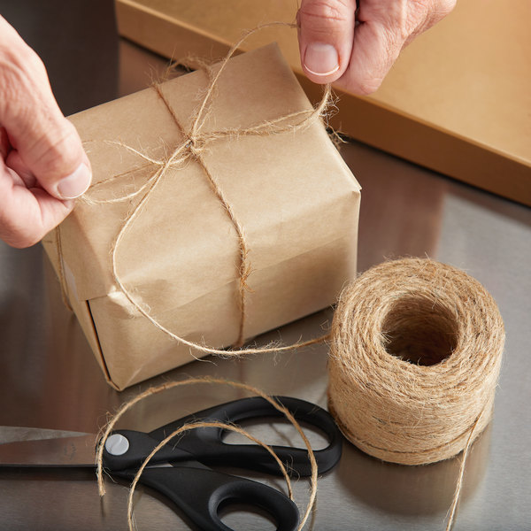 Hands tying natural twine around a box next to scissors and roll of twine