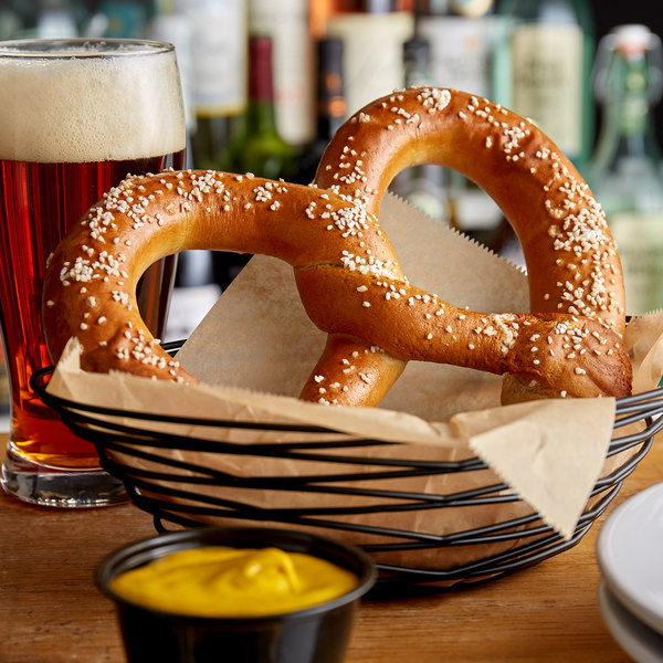 Large soft pretzel in basket with beer and mustard
