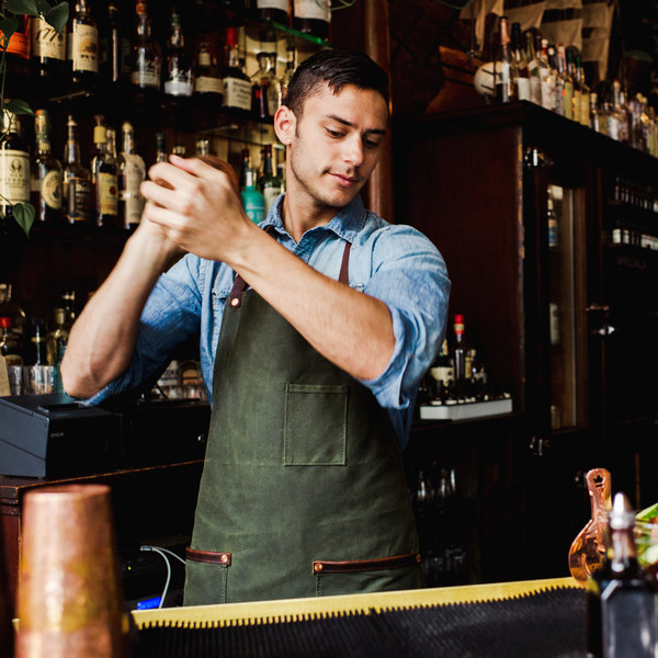 Bartender shaking a cocktail wearing a green waxed canvas apron