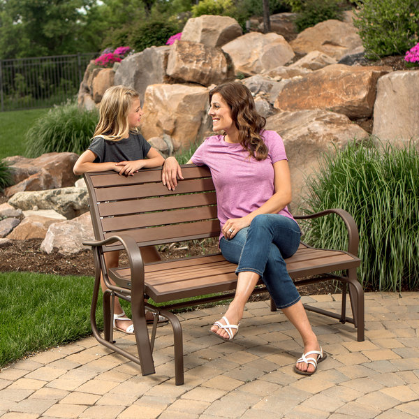 Lifetime brown glider bench with a woman sitting and a child standing behind it
