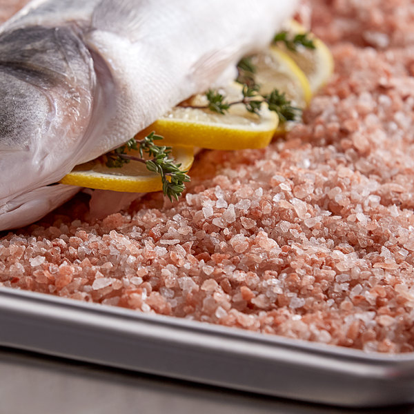 Himalayan salt lined in a baking sheet with fish, lemon, and thyme on top