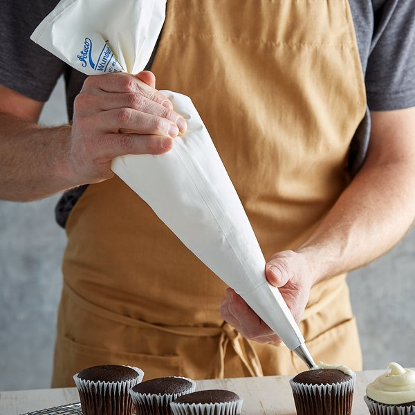 Baker using a polyurethane-lined cotton pastry bag to decorate cupcakes