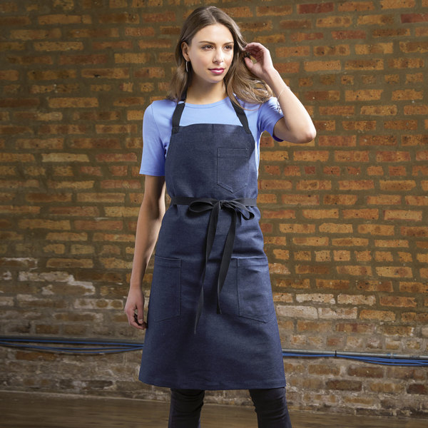 Woman standing in front of brown brick wall with black bib apron