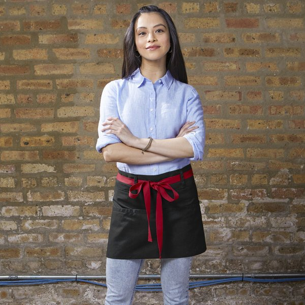 Woman standing in front of brown brick wall with blue outfit and black server apron with red tie