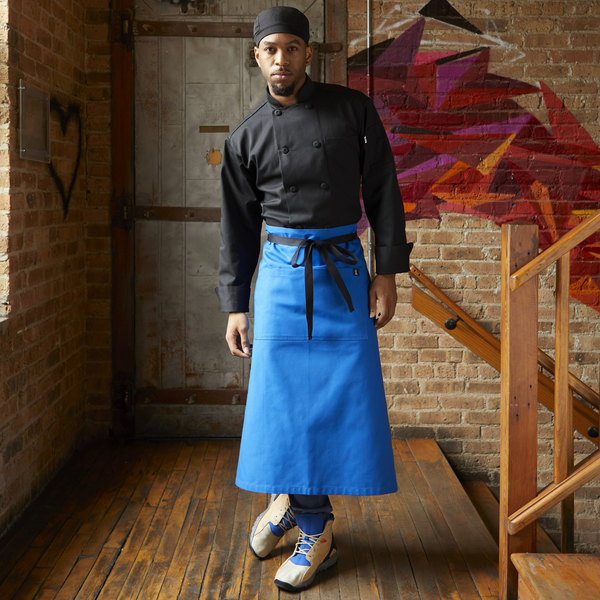 Man standing in front of brown brick wall with blue bistro apron with black tie