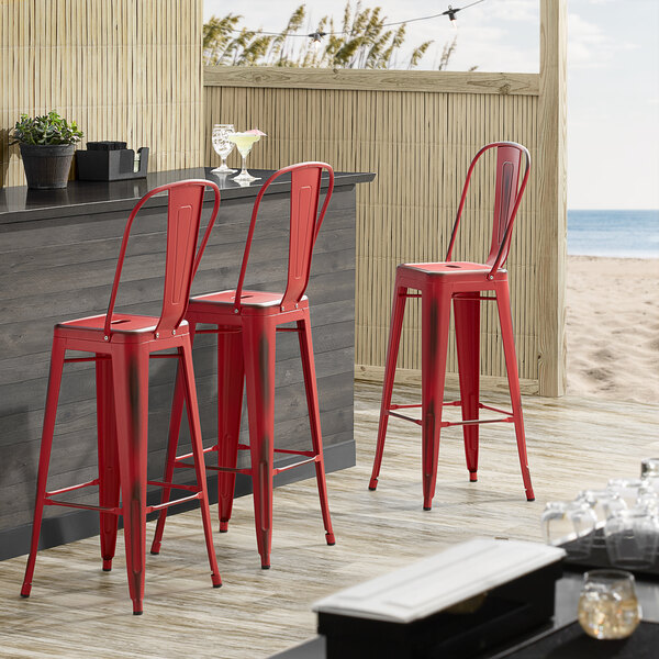 Lancaster Table & Seating Alloy Series Distressed Red Metal Indoor / Outdoor Industrial Cafe Barstool with Vertical Slat Back and Drain Hole Seat Main Image 4