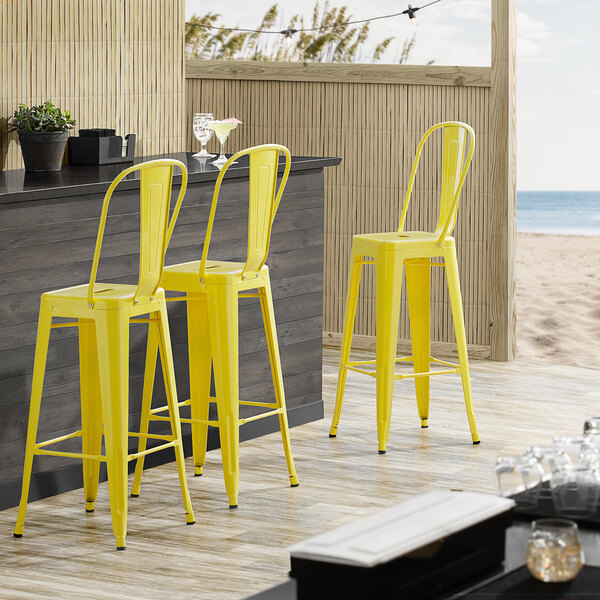 Lancaster Table & Seating Alloy Series Yellow Metal Indoor / Outdoor Industrial Cafe Barstool with Vertical Slat Back and Drain Hole Seat Main Image 4