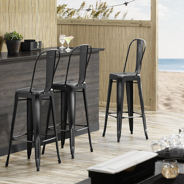 Lancaster Table & Seating Alloy Series Distressed Black Metal Indoor / Outdoor Industrial Cafe Barstool with Vertical Slat Back and Drain Hole Seat Main Image 4