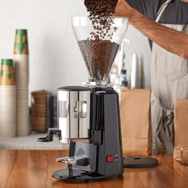 Barista pouring whole bean coffee into a commercial coffee grinder