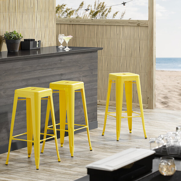 Lancaster Table & Seating Alloy Series Yellow Stackable Metal Indoor / Outdoor Industrial Barstool with Drain Hole Seat Main Image 3