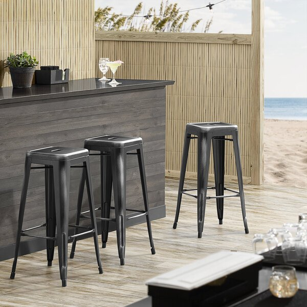 Lancaster Table & Seating Alloy Series Distressed Black Stackable Metal Indoor / Outdoor Industrial Barstool with Drain Hole Seat Main Image 3
