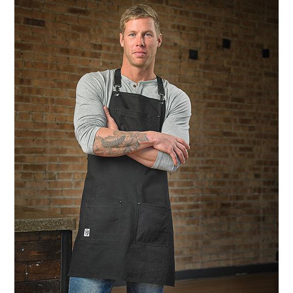 "Mercer Culinary M63208BDBK Metro Edge Renegade Black Customizable Cotton Canvas Bib Apron with Adjustable Black Leather Cross-Back Straps, and 5 Pockets - 30 1/2""L x 25 1/4""W Main Image 4"