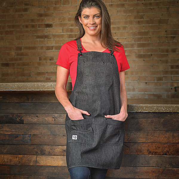 "Mercer Culinary M63208DENBR Metro Edge Renegade Black Customizable Cotton Denim Bib Apron with Adjustable Brown Leather Cross-Back Straps, and 5 Pockets - 30 1/2""L x 25 1/4""W Main Image 4"