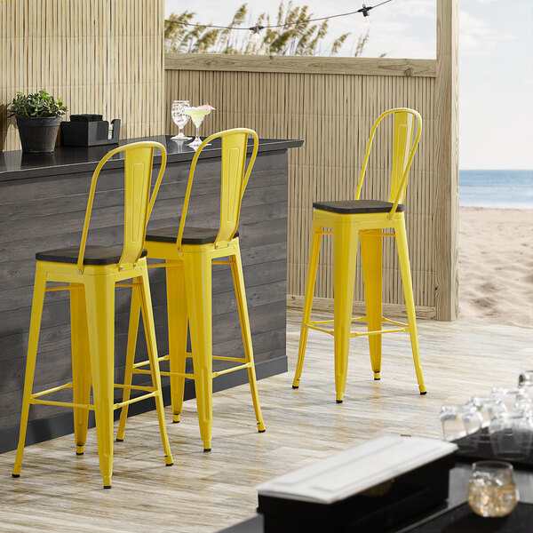 Lancaster Table & Seating Alloy Series Yellow Metal Indoor Industrial Cafe Bar Height Stool with Vertical Slat Back and Black Wood Seat Main Image 4