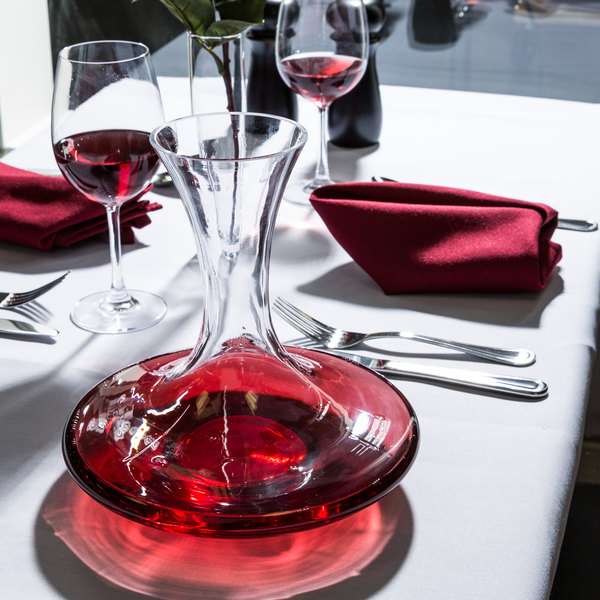 Wine decanter beside two glasses of red wine on elegant table