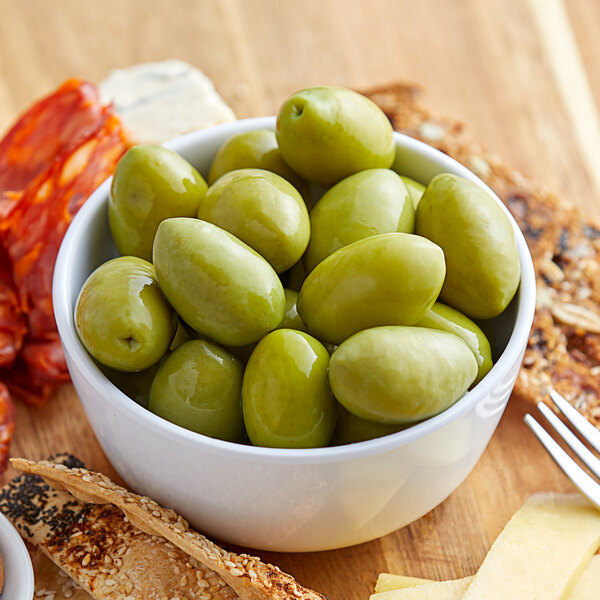 Green cerignola olives in a bowl surrounded by other snacks