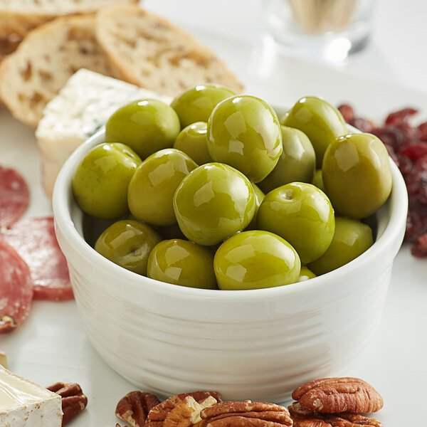 Round, green castelvetrano olives in a bowl surrounded by charcuterie