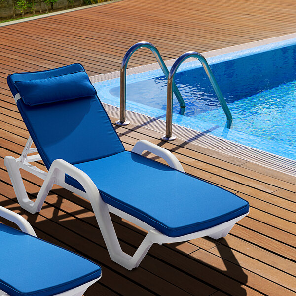 Lancaster Table and Seating white chaise lounge with a blue cushion poolside