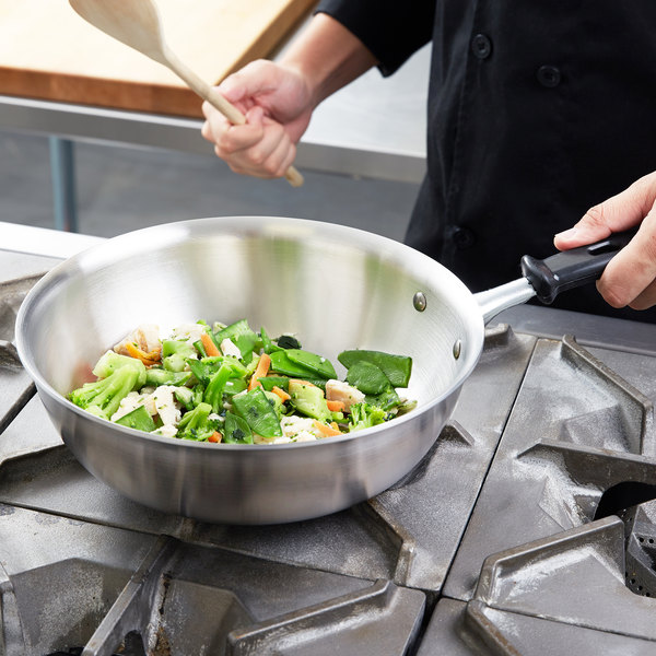Saucier pan with a stir fry on a gas stove