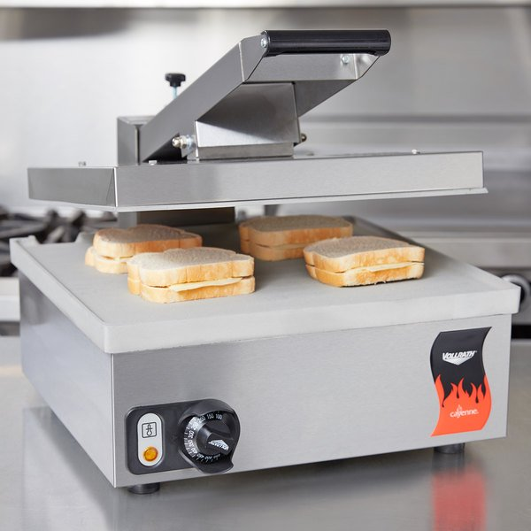 Vollrath panini grill with aluminum plates, sitting on a table