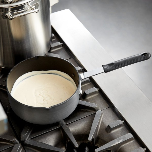 Dark non-stick sauce pan with a white sauce inside sitting on a stove