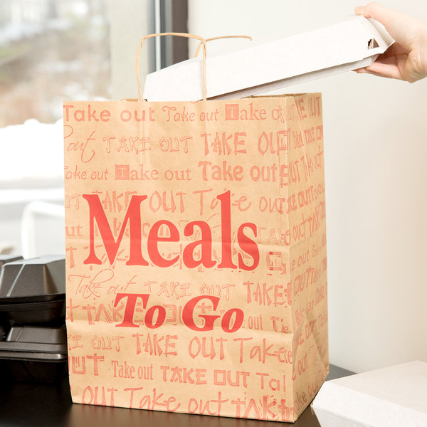 Person putting packaged food in a paper bag