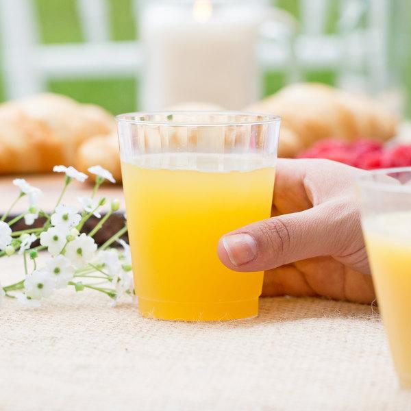Plastic glass of fresh orange juice in brunch setting