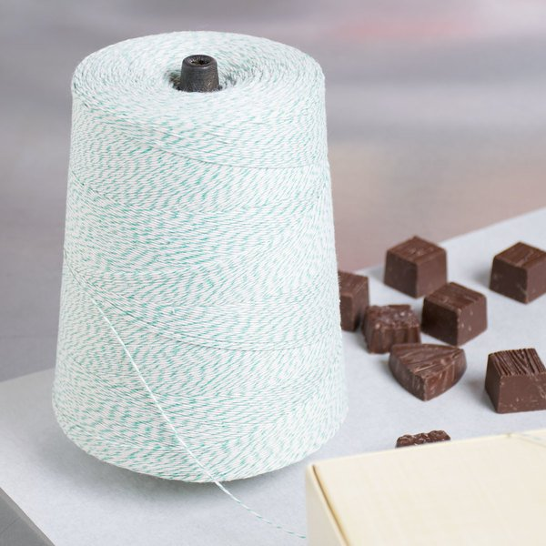 Large roll of green and white polyester / cotton twine next to chocolates