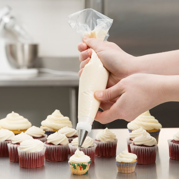 Baker icing cupcakes with a high-grip disposable pastry bag