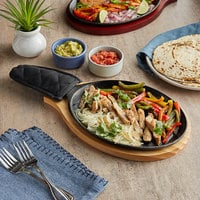 Choice 9 1/4 inch x 7 inch Oval Pre-Seasoned Cast Iron Fajita Skillet with Natural Finish Wood Underliner and Black Cotton Handle Cover