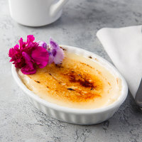 Acopa 5 oz. Oval Bright White Fluted Porcelain Souffle / Creme Brulee Dish - 12/Pack