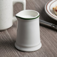 Tuxton DNR-0351 DuraTux 3.5 oz. Ivory (American White) Unhandled Creamer with Green Band - 12/Case