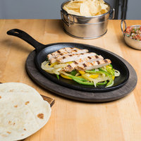Lodge 10 inch x 7 1/2 inch Pre-Seasoned Cast Iron Oval Fajita Skillet with Handle and Walnut Wood Underliner