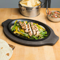 Lodge 10 inch x 7 inch Pre-Seasoned Cast Iron Oval Fajita Skillet with Grip Style Walnut Wood Underliner
