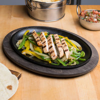 Lodge 10 inch x 7 inch Pre-Seasoned Cast Iron Oval Fajita Skillet with Walnut Wood Underliner