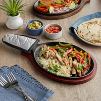 Choice 9 1/4 inch x 7 inch Oval Pre-Seasoned Cast Iron Fajita Skillet with Mahogany Finish Wood Underliner and Grey Silicone Coated Handle Cover