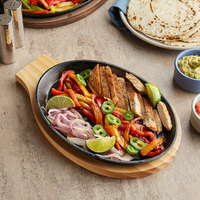 Choice 9 1/4 inch x 7 inch Oval Pre-Seasoned Cast Iron Fajita Skillet with Natural Finish Wood Underliner