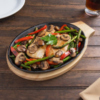 Valor 9 inch x 7 inch Oval Pre-Seasoned Cast Iron Fajita Skillet with Natural Finish Wood Underliner