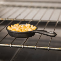 Cast iron skillet in oven, filled with macaroni and cheese
