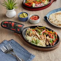 Choice 9 1/4 inch x 7 inch Oval Pre-Seasoned Cast Iron Fajita Skillet with Oak Finish Wood Underliner and Chili Pepper Cotton Handle Cover