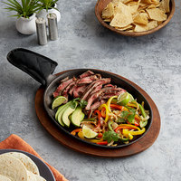 Valor 13 inch x 10 inch Oval Pre-Seasoned Cast Iron Fajita Skillet with Rustic Chestnut Finish Rubberwood Underliner and Black Cotton Handle Cover